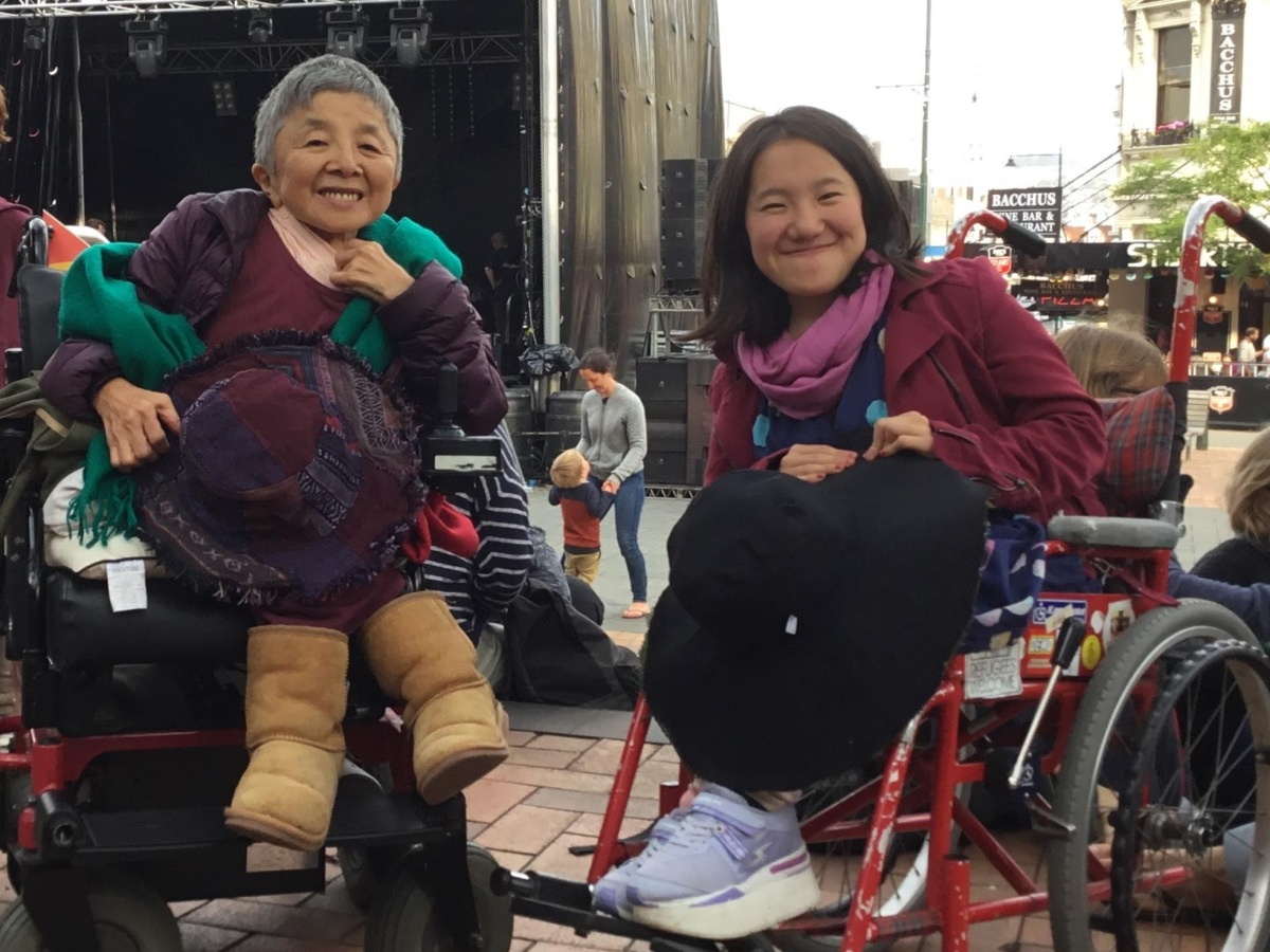 A Japanese mother and daughter both using wheelchairs. They sit in front of a New Year's Concert stage in the city centre.
